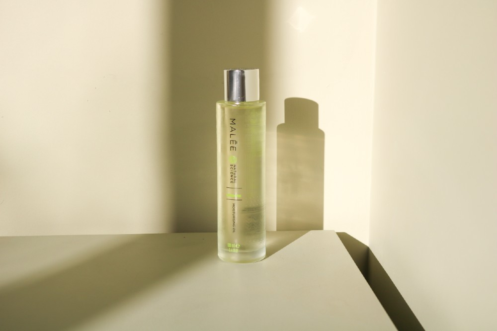 Malée Natural Science 100ml Verdure Moisturising Body Oil with its reflection on a table
