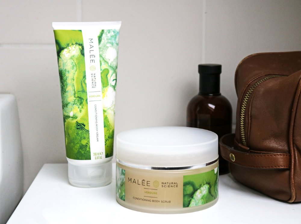 Malée Natural Science Verdure 200ml Conditioning Body Cream Verdure Conditioning Body Scrub with a zipped brown bag and a sealed amber glass bottle on top of a white stand.